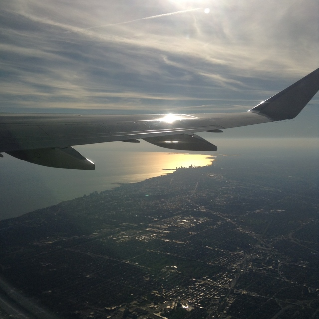 Chicago from above. Navy Pier in the glow below the wing.